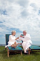 Senior couple having drinks on lawn chairs