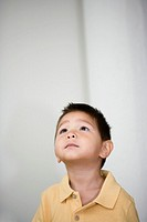 Close up of young Asian boy looking up indoors