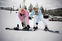 Young women strapping boots to snowboards