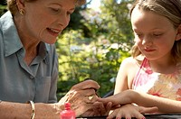 Grandmother painting granddaughterÆs fingernails