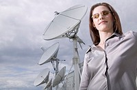 Businesswoman standing near satellite dishes
