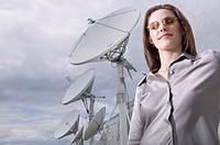 Businesswoman standing near satellite dishes