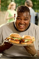 African man eating two hamburgers