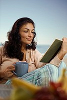 Hispanic woman reading book