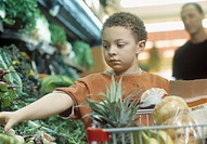 Young African boy with shopping cart in produce aisle