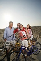 Mature couples with bicycles on beach boardwalk