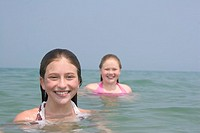 Two young girls swimming in ocean