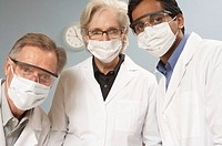 Scientists wearing surgical masks and safety glasses