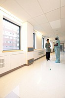Male surgeon and woman talking in hospital hallway