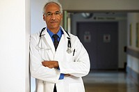 Male African doctor leaning on wall