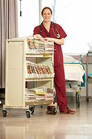 Nurse standing with push cart of medical records