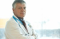Male doctor standing in front of hospital window