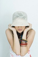 Teenage girl pulling hat down over eyes, portrait