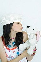 Teenage girl puckering lips at stuffed animal, portrait