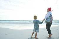 Senior woman standing on beach with grandson
