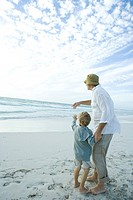 Senior man standing on beach with grandson, pointing toward distance