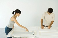 Woman painting door while man applies masking tape
