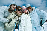 Young skiers standing on ski slope, portrait