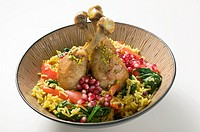Chicken legs with saffron rice and pomegranate seeds
