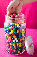 Hand taking coloured bubble gum balls out of jar