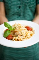 Woman holding plate of spaghetti with Parmesan and basil
