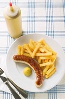 Sausage with chips and mustard on plate in restaurant