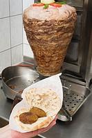 Falafel chick-pea balls in pita bread, döner behind