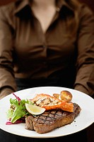 Woman holding plate of Surf & Turf beef steak with prawn