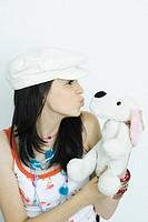 Teen girl puckering at stuffed animal, portrait