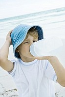 Boy drinking water on beach