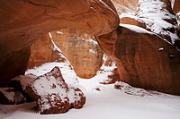 A late winter storm covers the sand in between fins at Sand Dune Arch with a thin layer of fresh snow, Arches National Park, Utah, USA