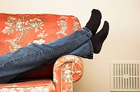 Abstract shot of person's legs crossed while relaxing on a sofa