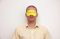 Young businessman gabbing a moments shut eye wearing an eye mask