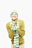 Young woman in knit hat, scarf and gloves looking up, smiling