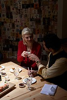 Young man and woman toasting with sake in sushi bar