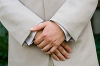 Groom standing with hands clasped, mid section