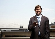 Businessman looking at mobile phone outdoors, smiling