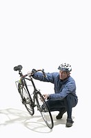 Mature man checking tyre on bicycle