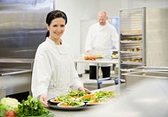 Two chefs in commercial kitchen focus on woman in foreground