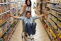 Young couple, man sitting in shopping trolley in supermarket