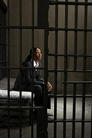 Young businesswoman sitting on bed in prison cell