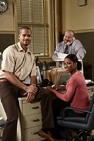Two men and woman working in office, portrait