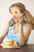Woman Looking Through Hole in Doughnut