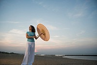 Woman on beach with paper umbrella