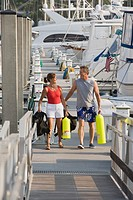 Couple walking on boat dock carrying scuba gear