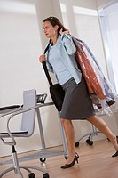 Woman carrying dry cleaning and briefcase