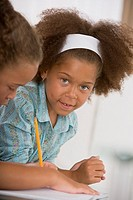 Girl leaning past sister writing in notebook