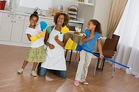 Mother and daughters playing with cleaning supplies