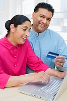 Woman and man with laptop and credit card