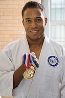 Man wearing gi holding medal